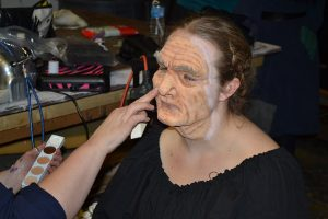 Make-up artist Kerri Rickard is working a mask onto Victoria Kaczmarek (Peddler Woman).